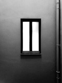 closed black framed window near wall