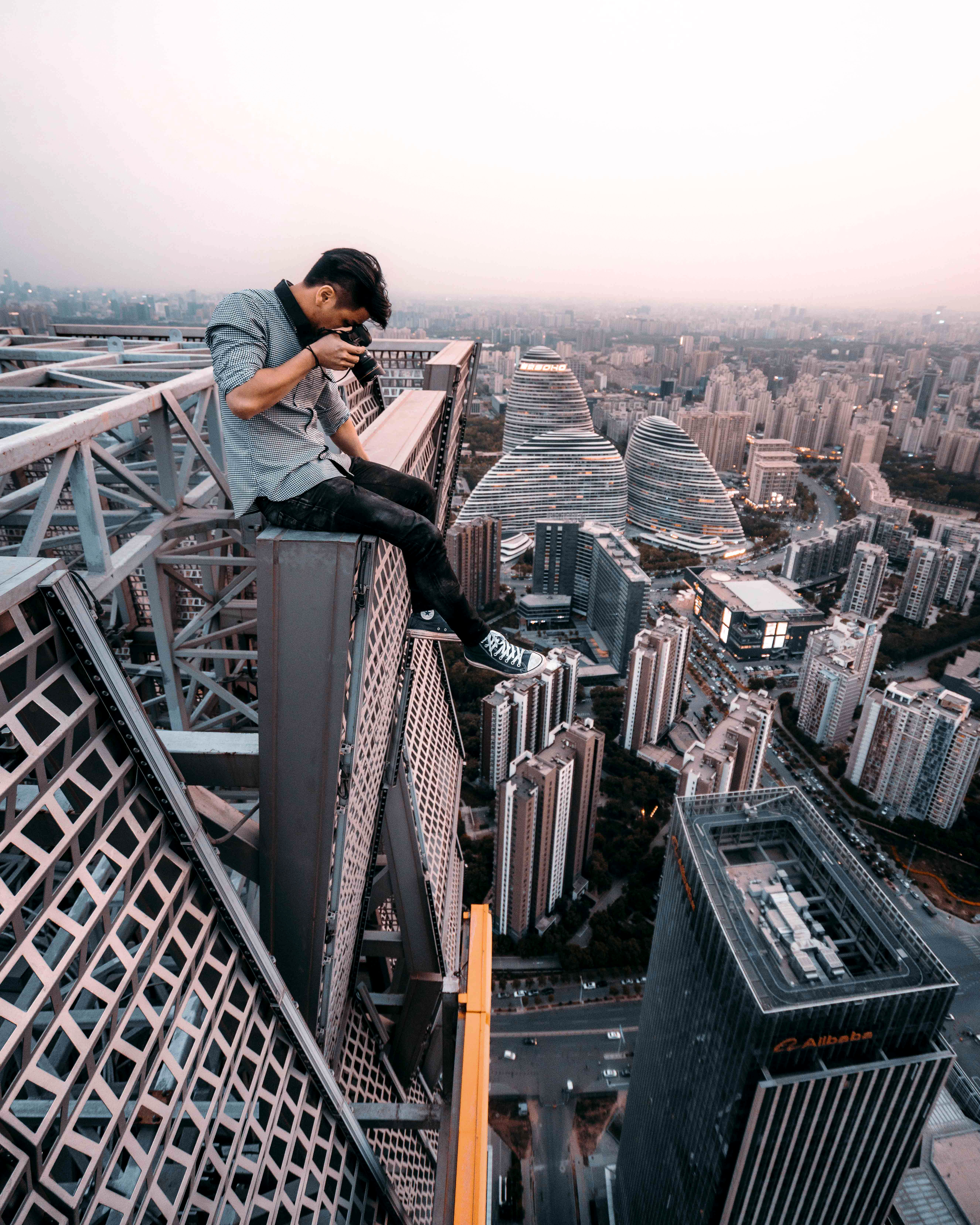 man sitting on top of building taking photo below