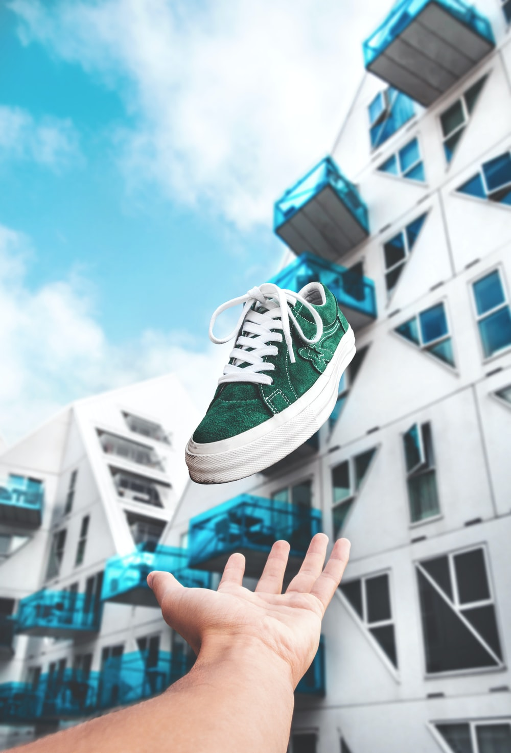 person throwing green and white low-top sneaker at daytime