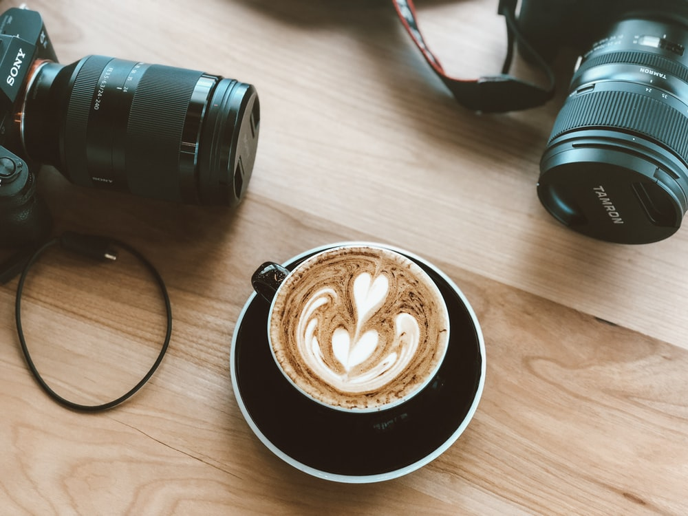 cappuccino on ceramic mug between two Sony and Tanron DSLR camera on brown wood surface