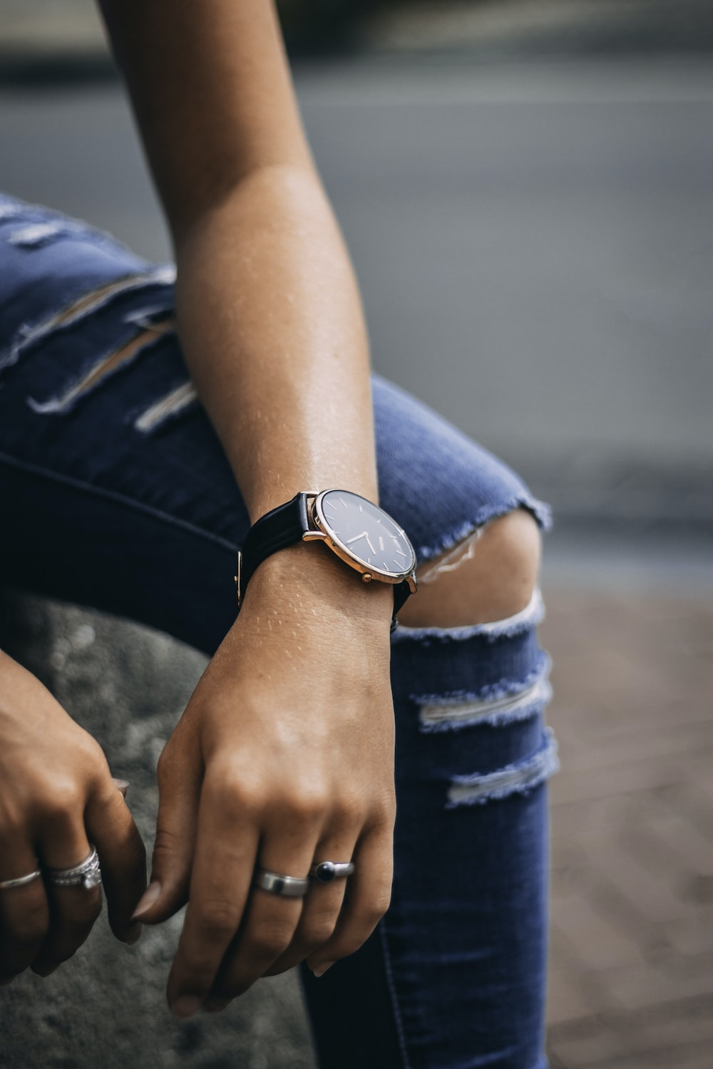sitting person wearing silver-colored analog watch