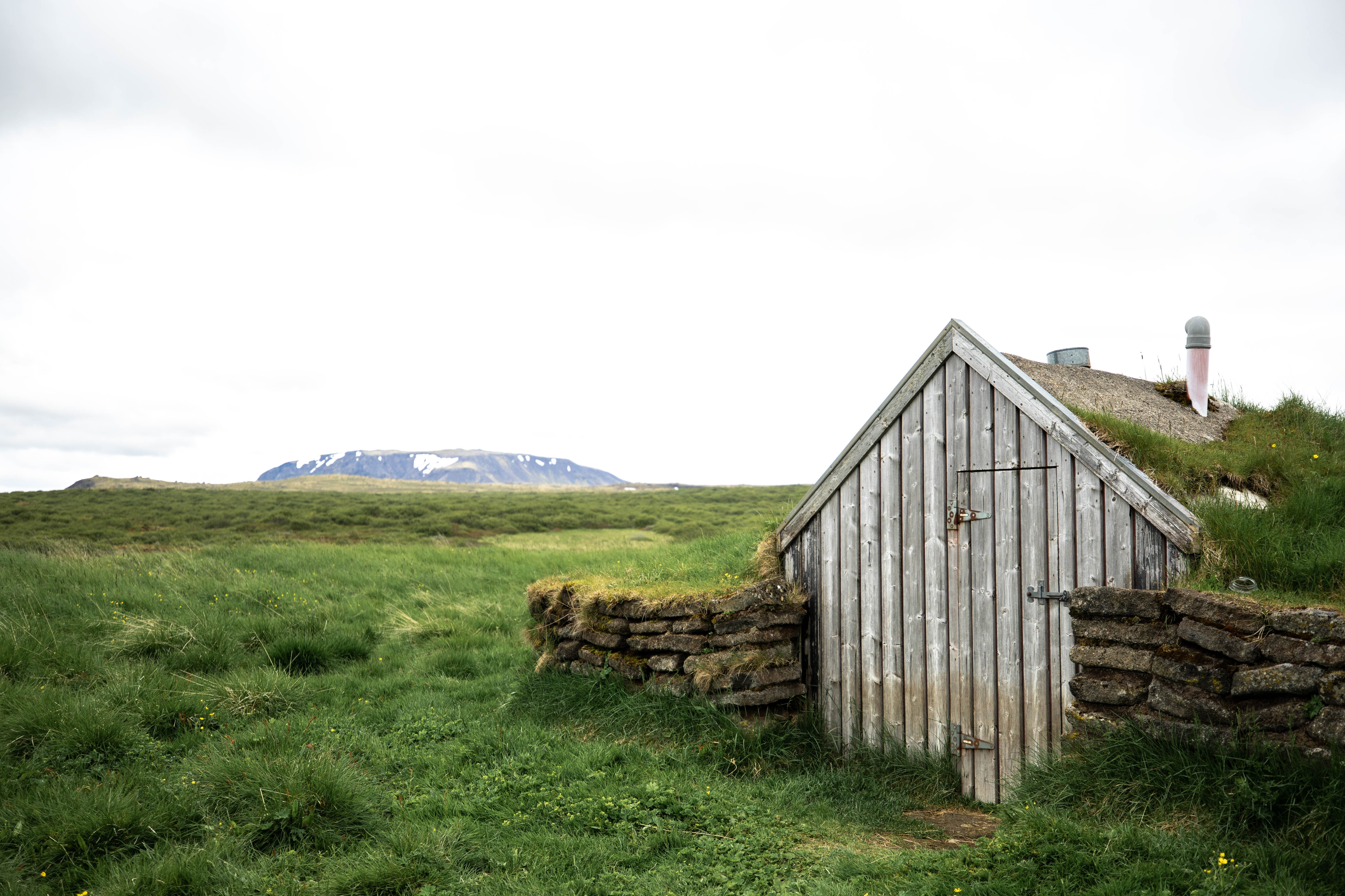 white wooden barn in the middle of field
