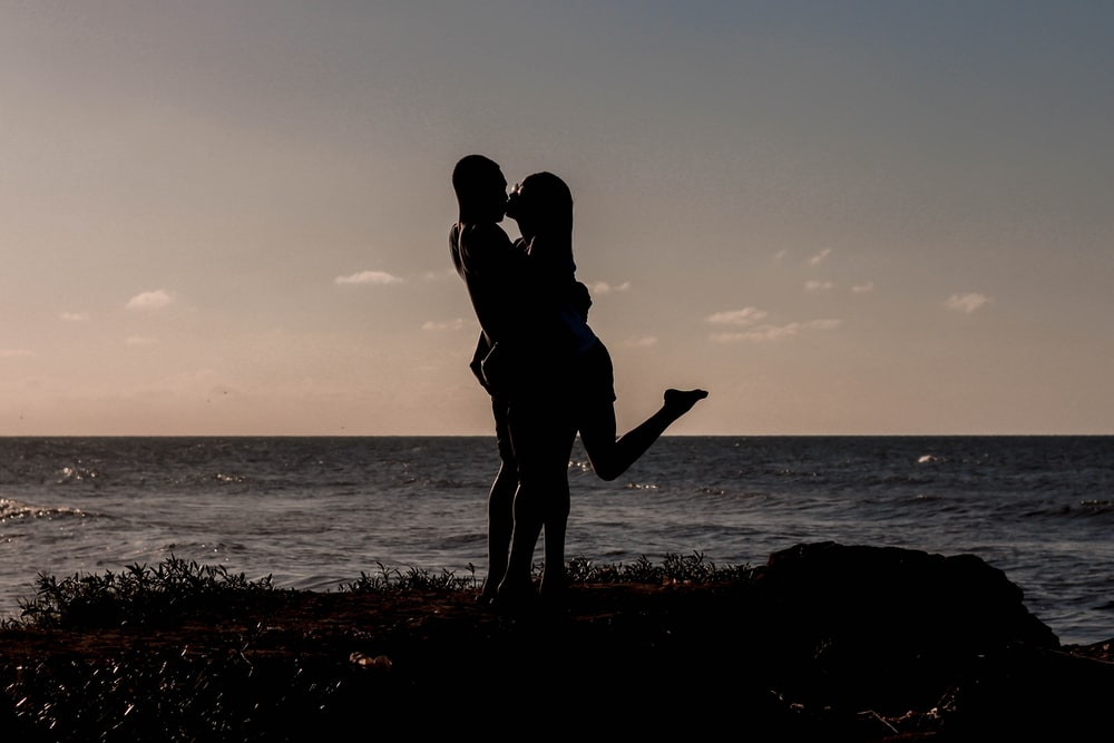 silhouette of kissing couples near sea