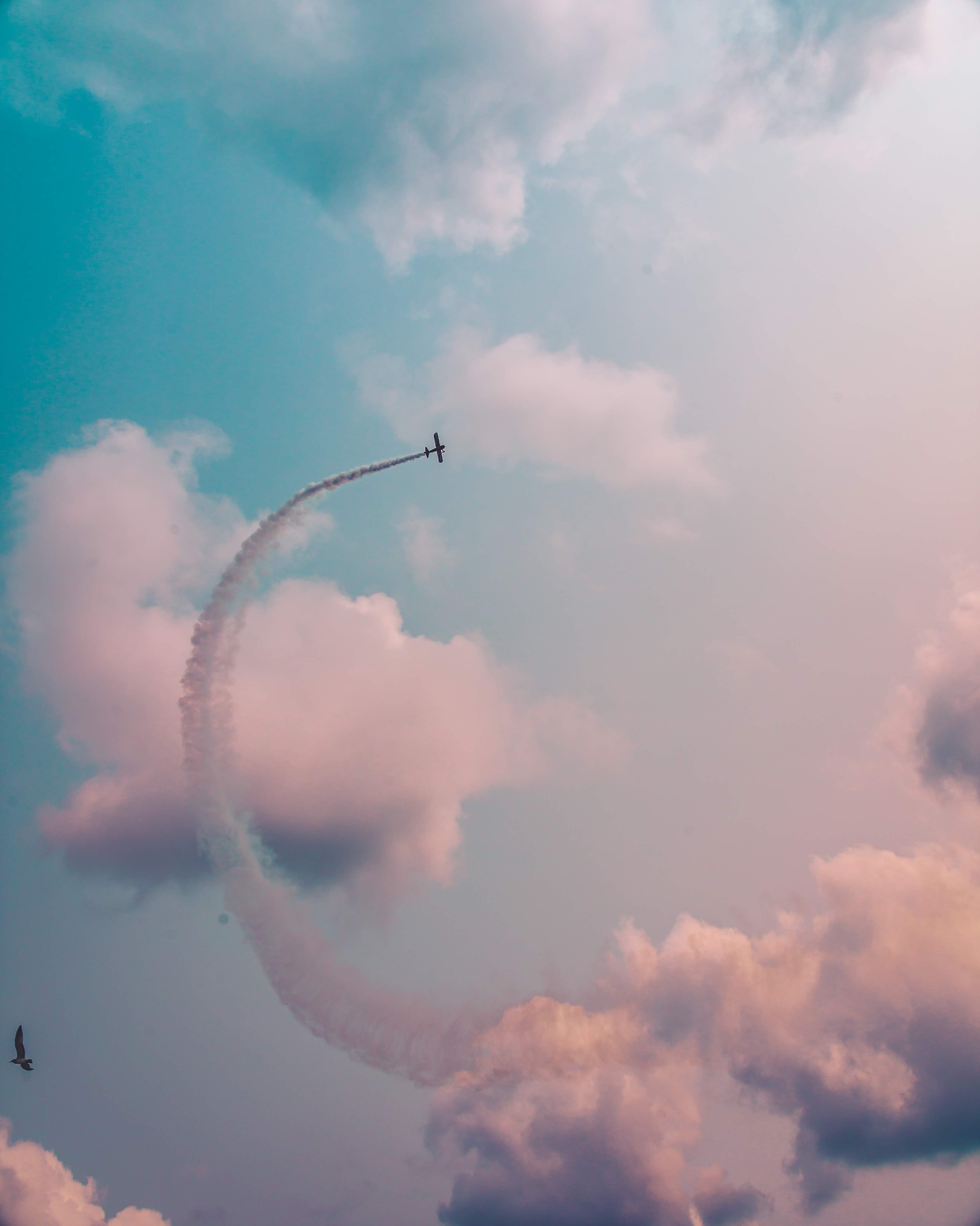 low angle photography of plane flying at high altitude with track of smoke during daytime