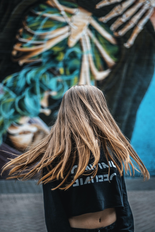 brown haired woman wearing black crop-top sweatshirt making a hair spin near green wall