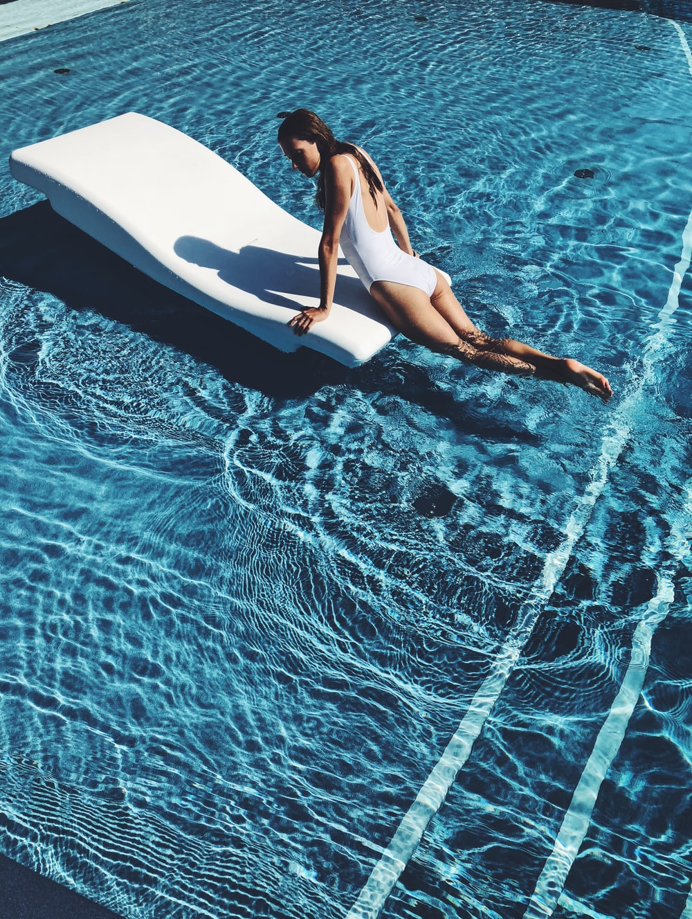 woman lying on white lounge chair in the middle of pool