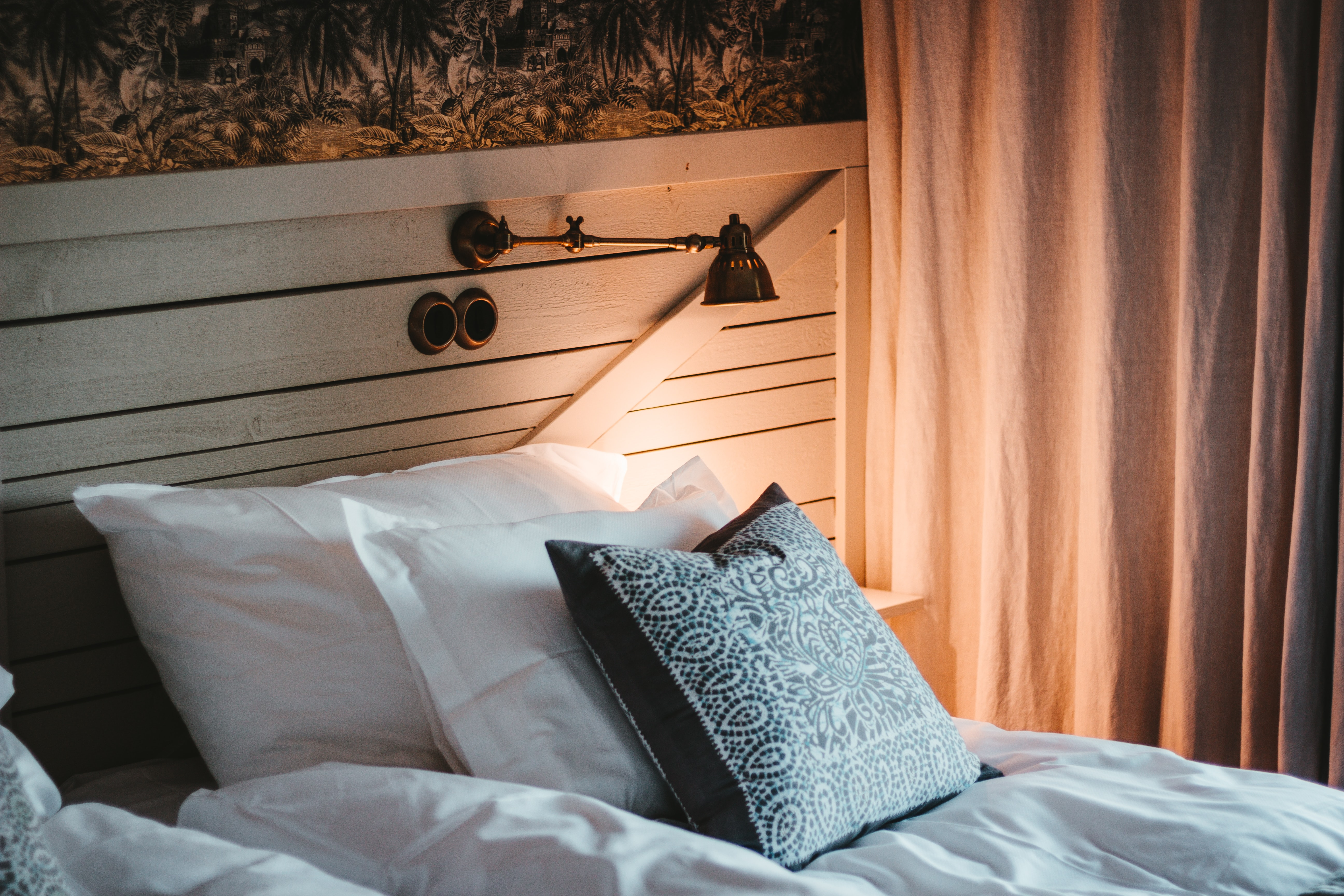 empty bed beside white curtain