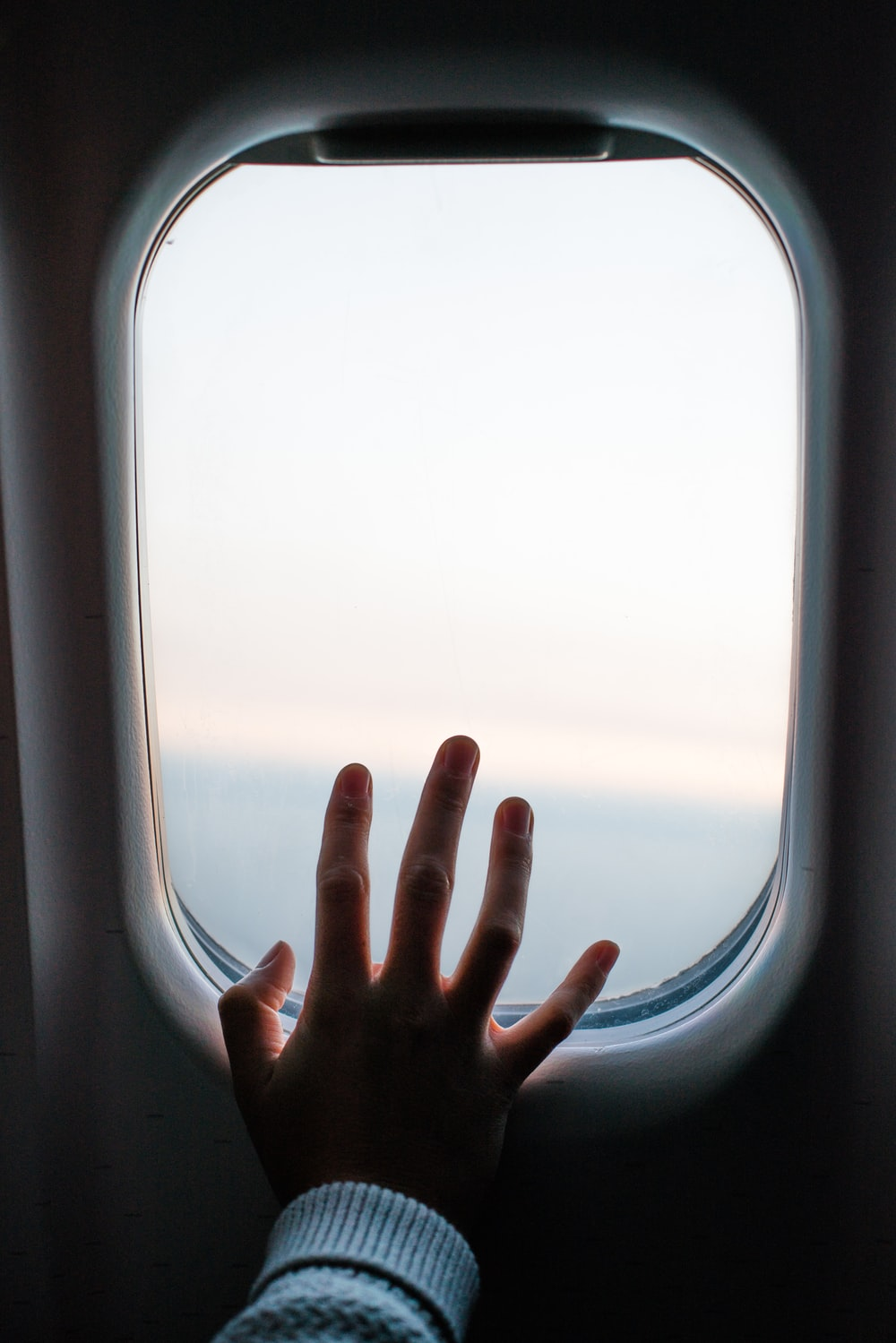 person touching airplane window