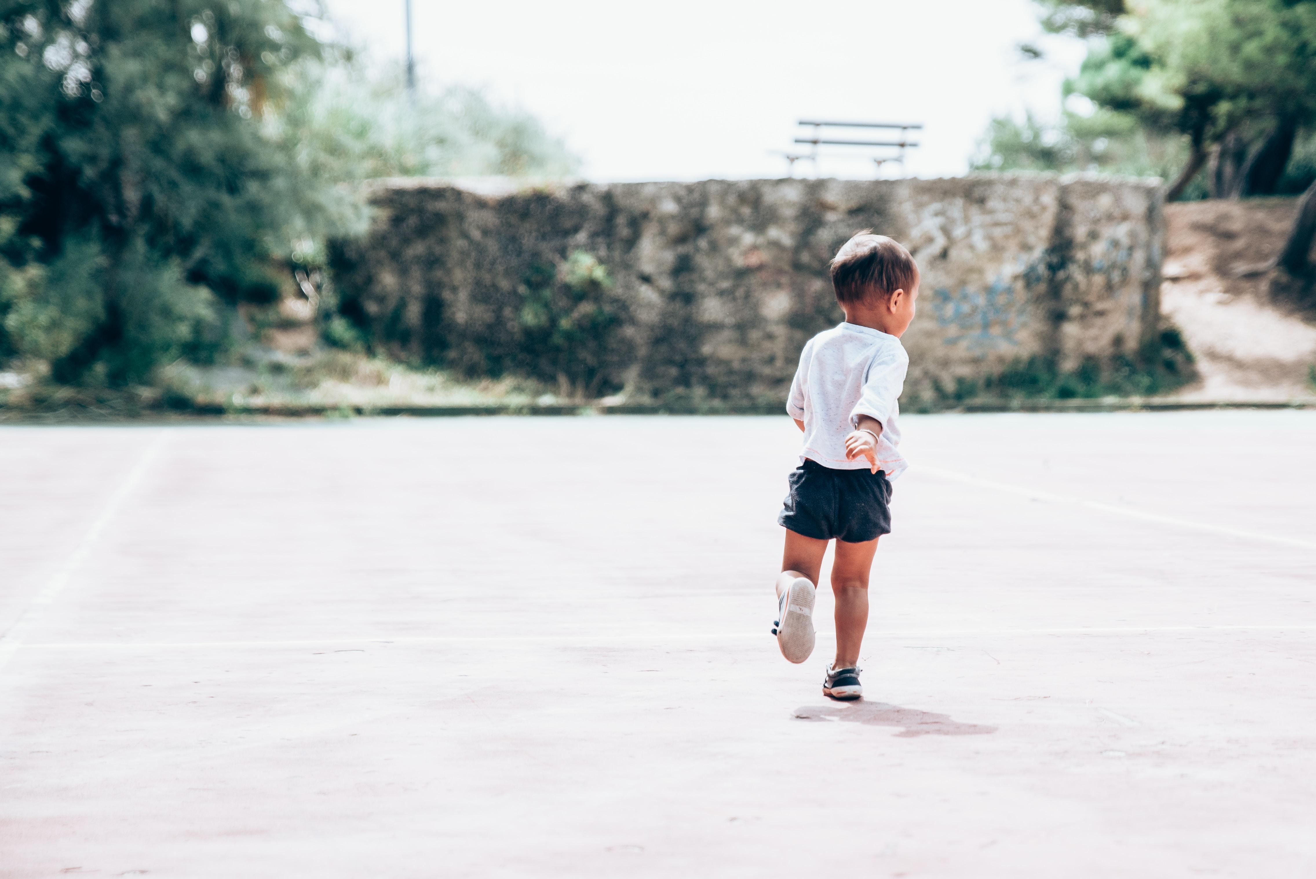 toddler running on gray concrete floor