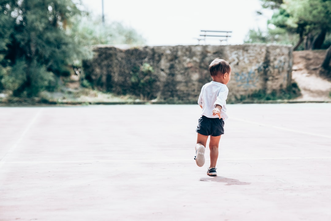 My joyful little boy running on a abandonned tennis court in south of france.