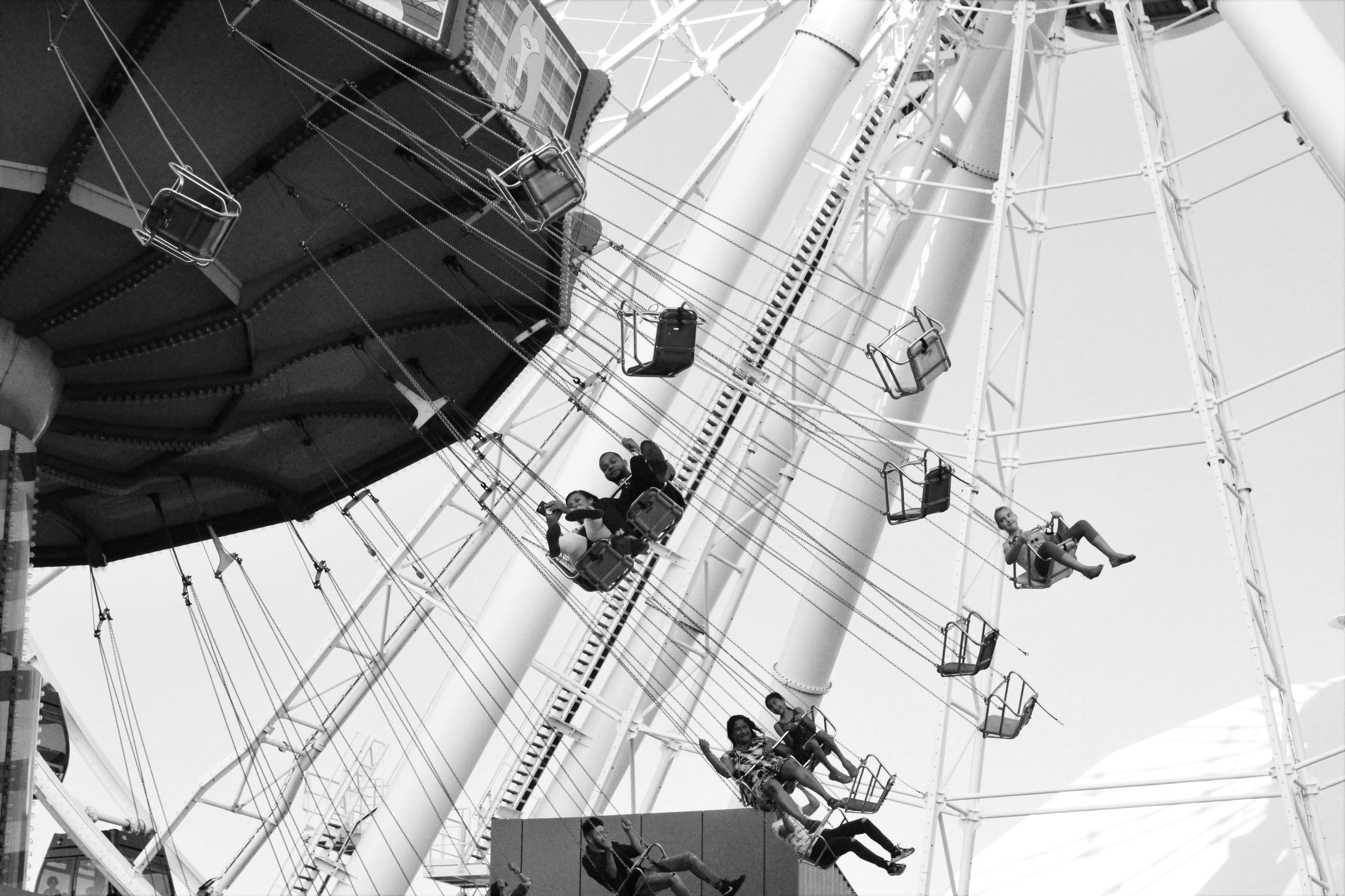 grayscale photo of people riding amusement park ride