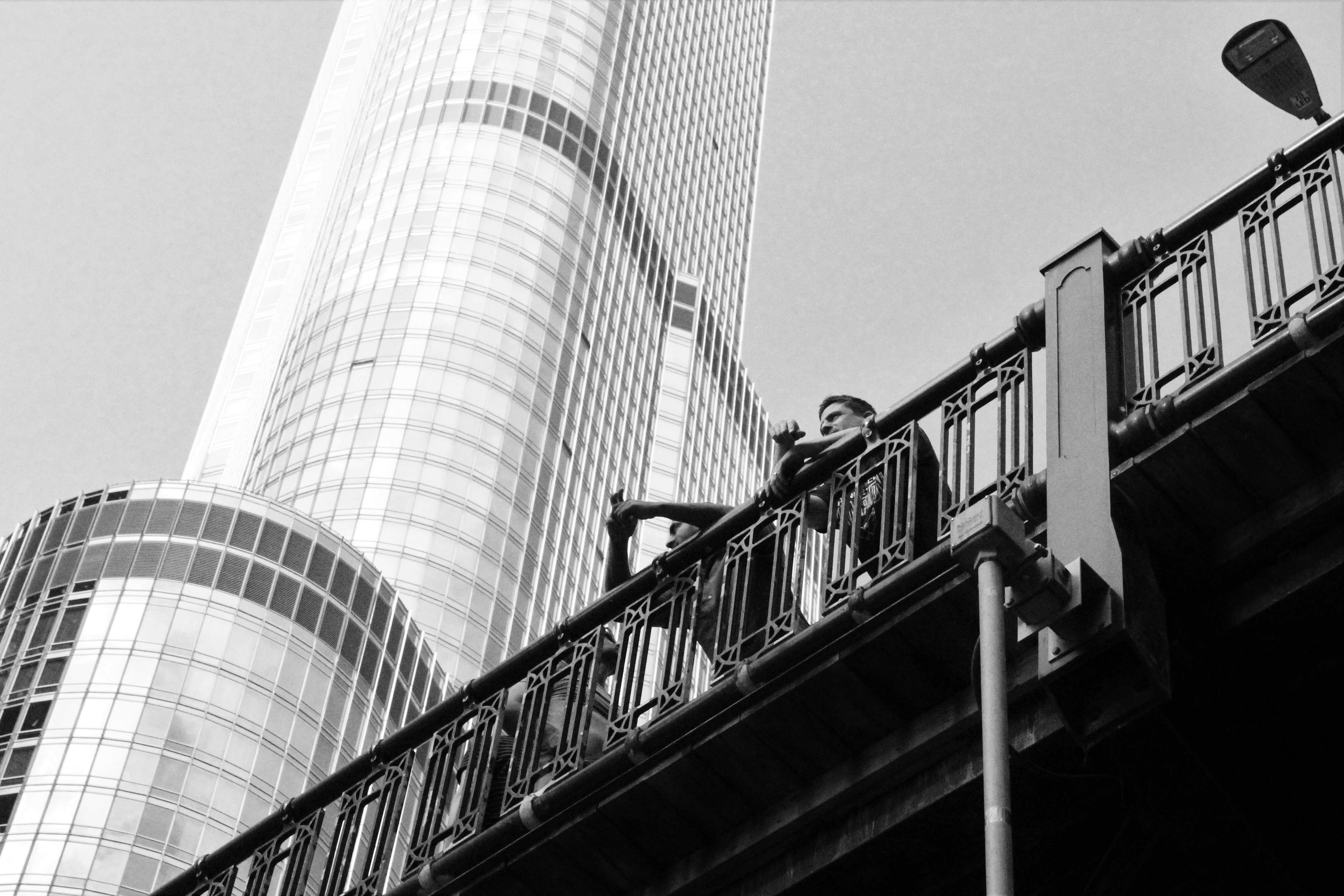 low-angle grayscale photography of two men leaning both arms on outdoor baluster beside high-rise building during daytime