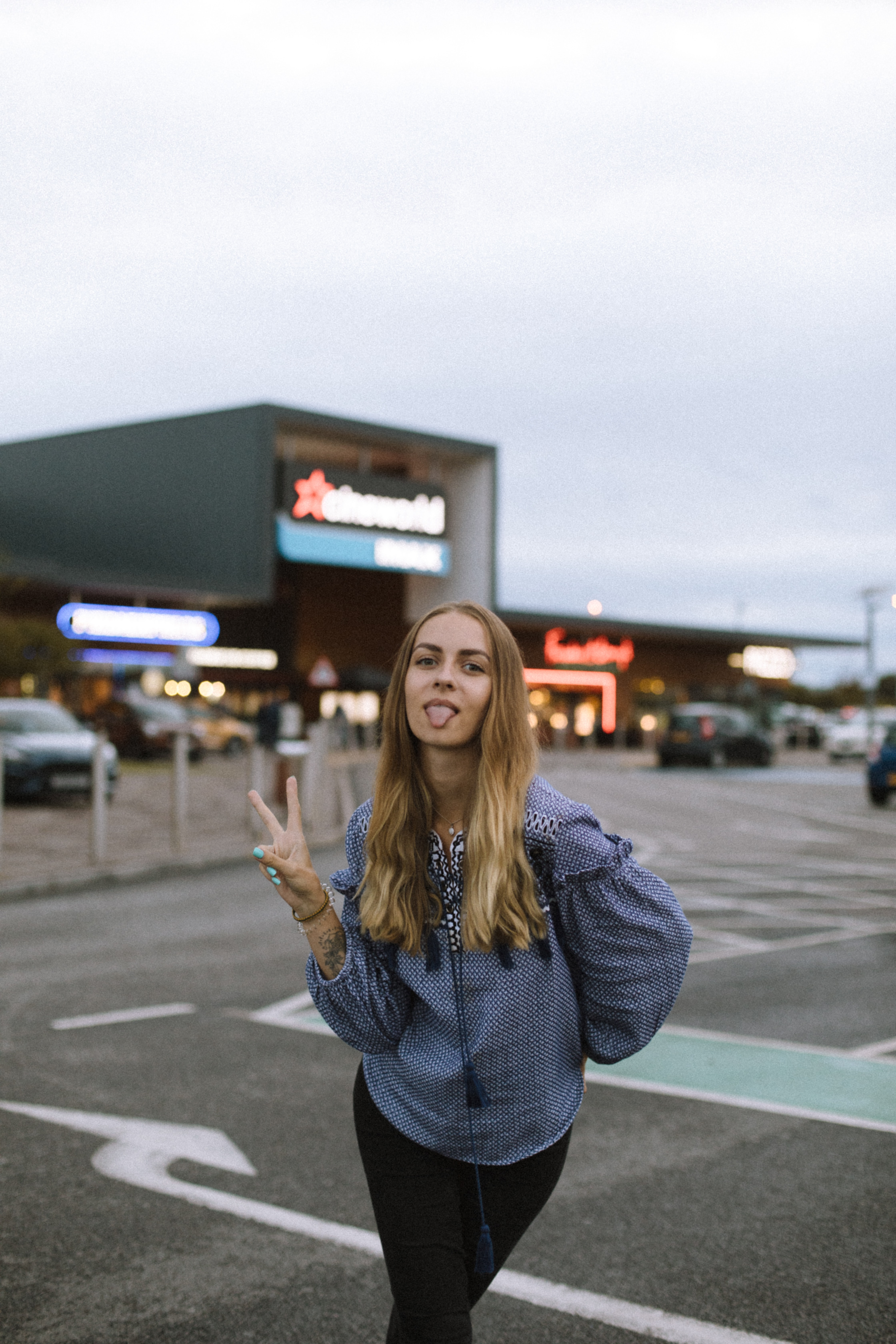 woman wearing blue jacket standing while doing peace hand sign