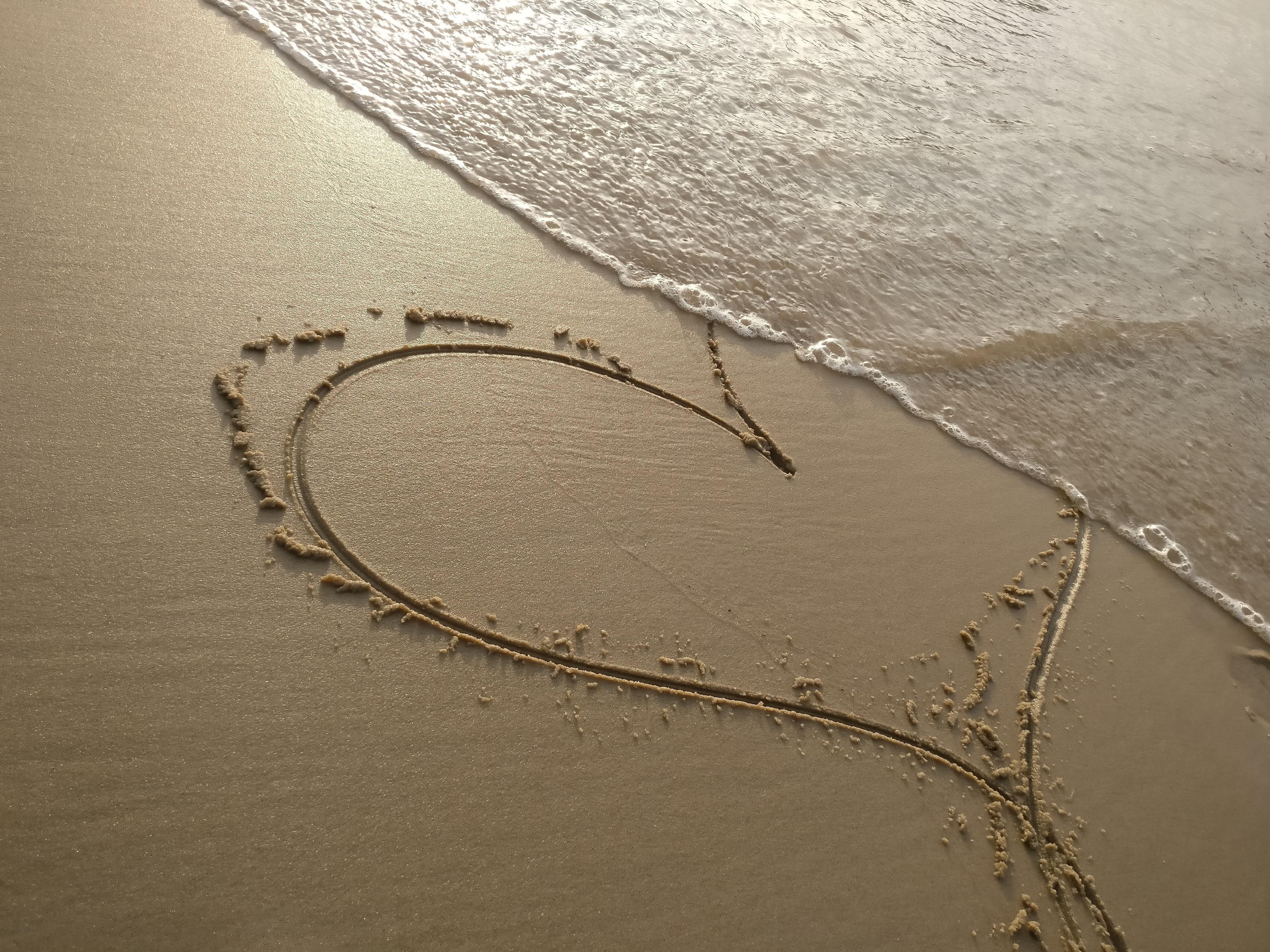 handwritten heart on sand