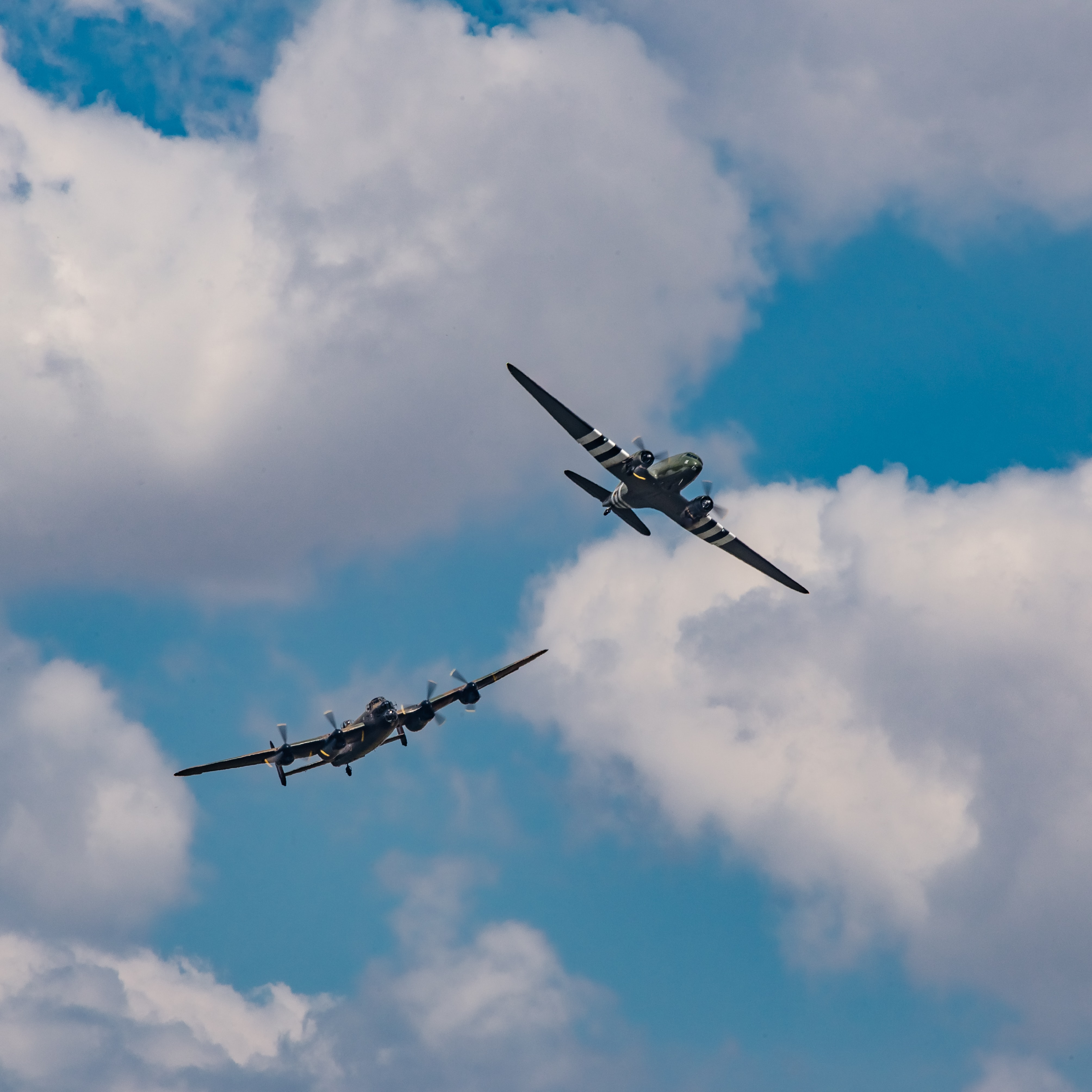 two planes under white clouds during daytime