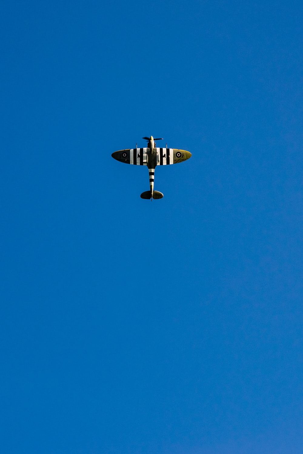 gray and white airplane under blue sky
