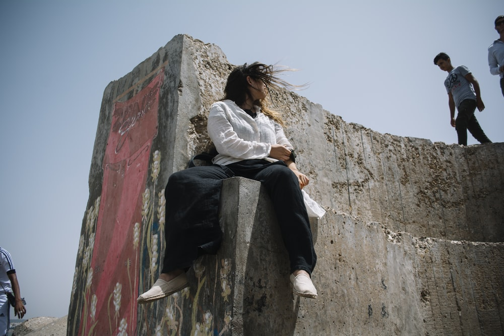 woman sitting on concrete wall