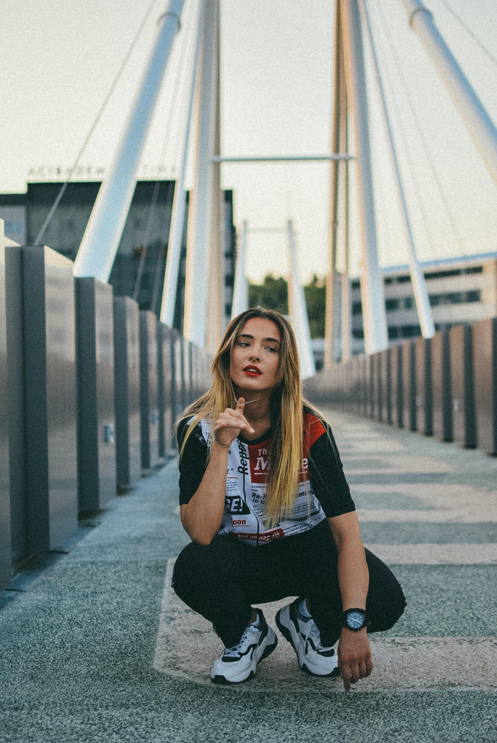 woman crouching on bridge at daytime
