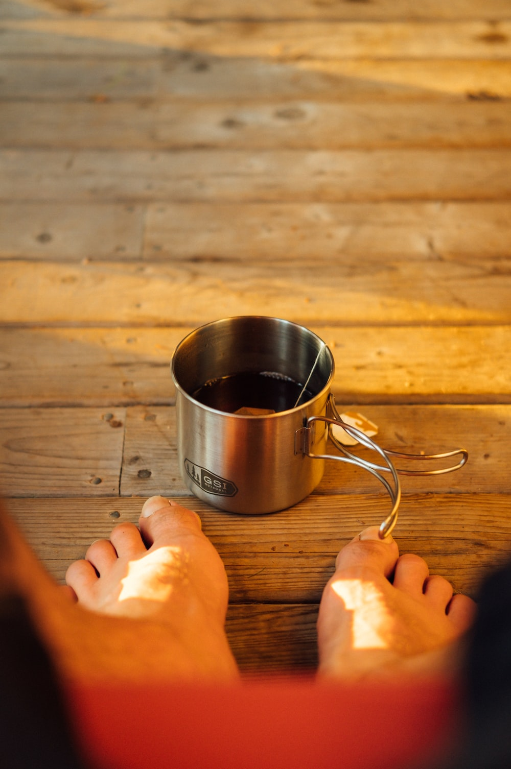 silver cup on brown wooden surface