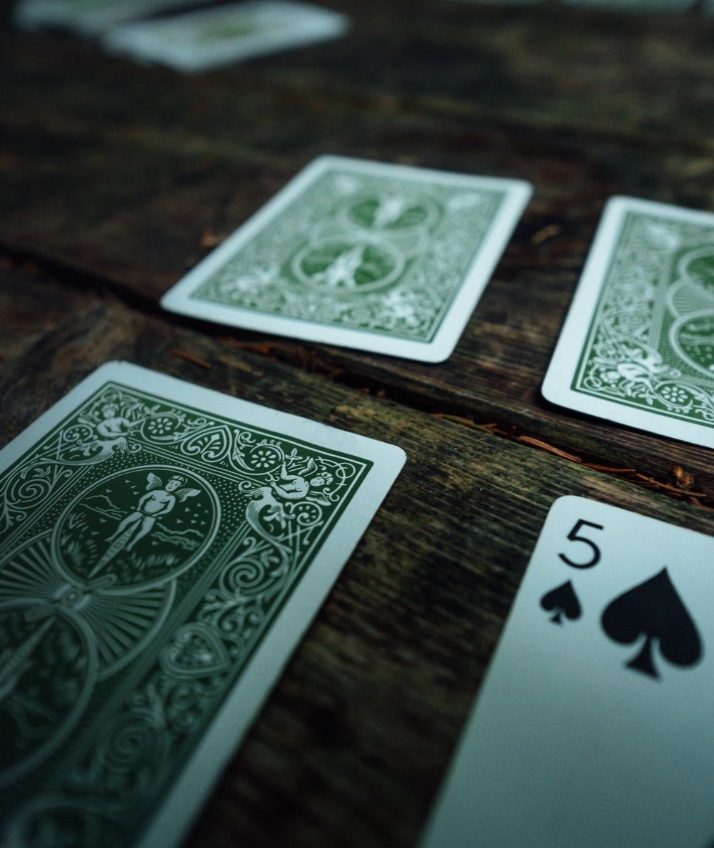 5 of spades playing opened on brown wooden surface