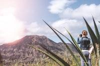 woman wearing blue denim jacket while taking photo of brown mountain