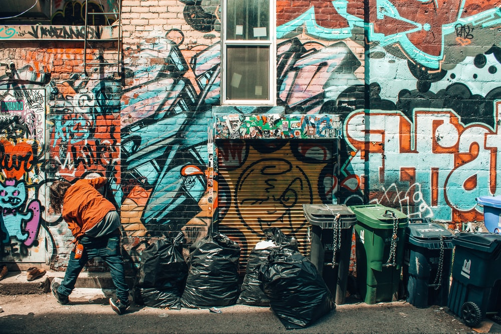 man standing in front of graffiti tagged wall beside trash bags and trash bins at daytime