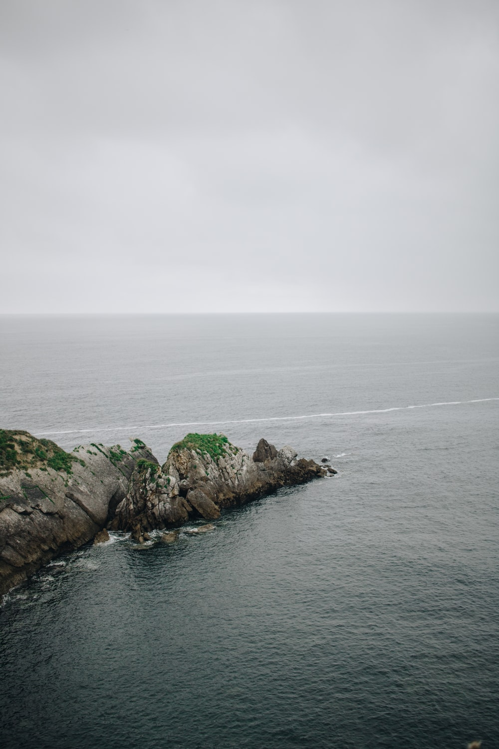 green and gray rock formation surrounded by water during daytime