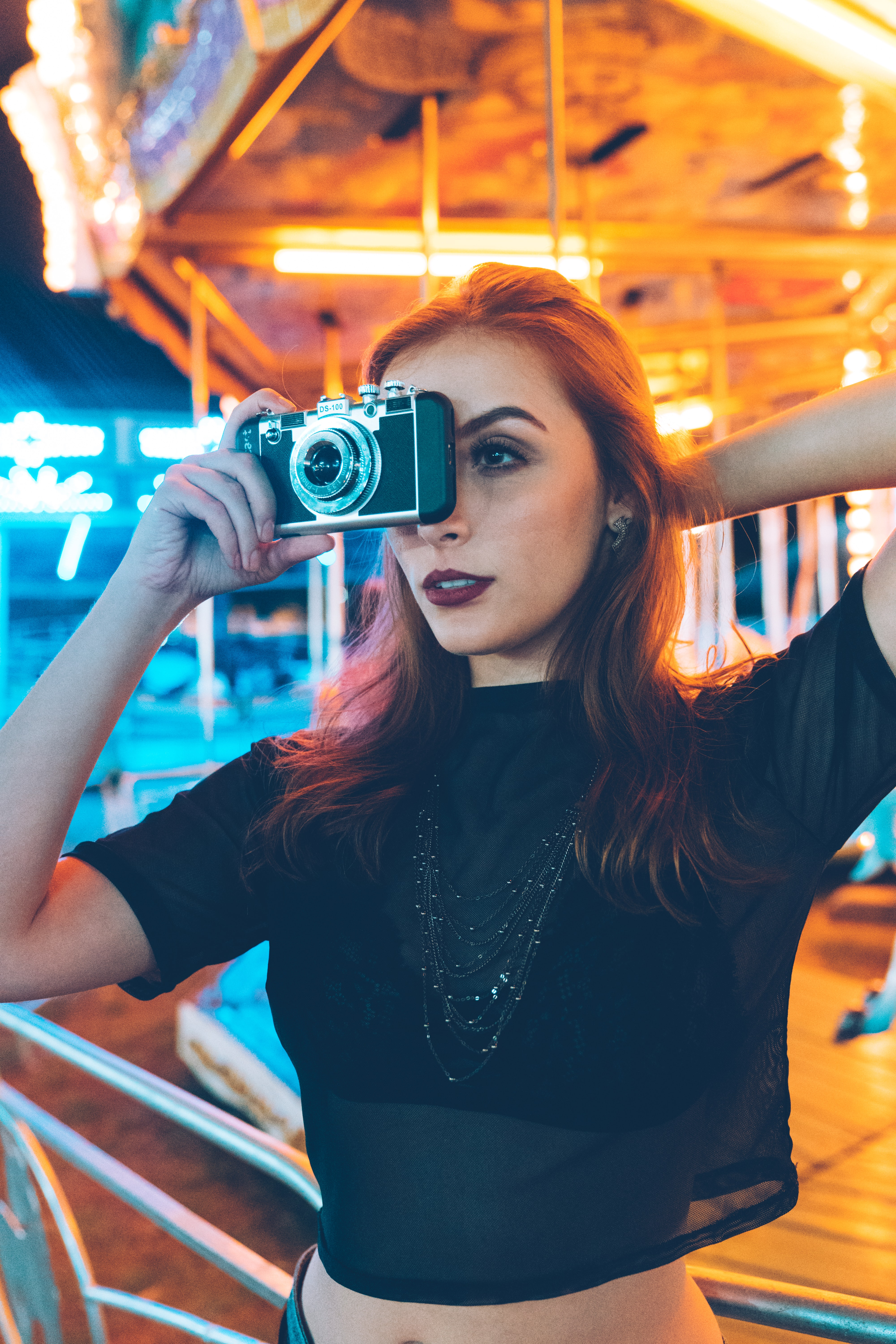 selective focus photo of woman holding black compact camera