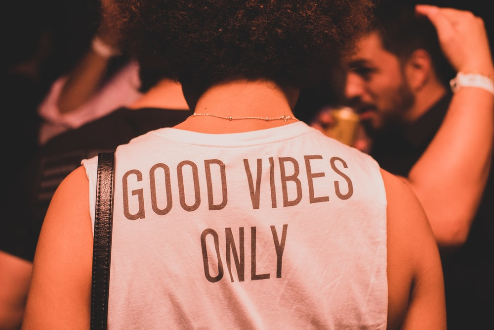 photo of person wearing white and brown good vibes only shirt