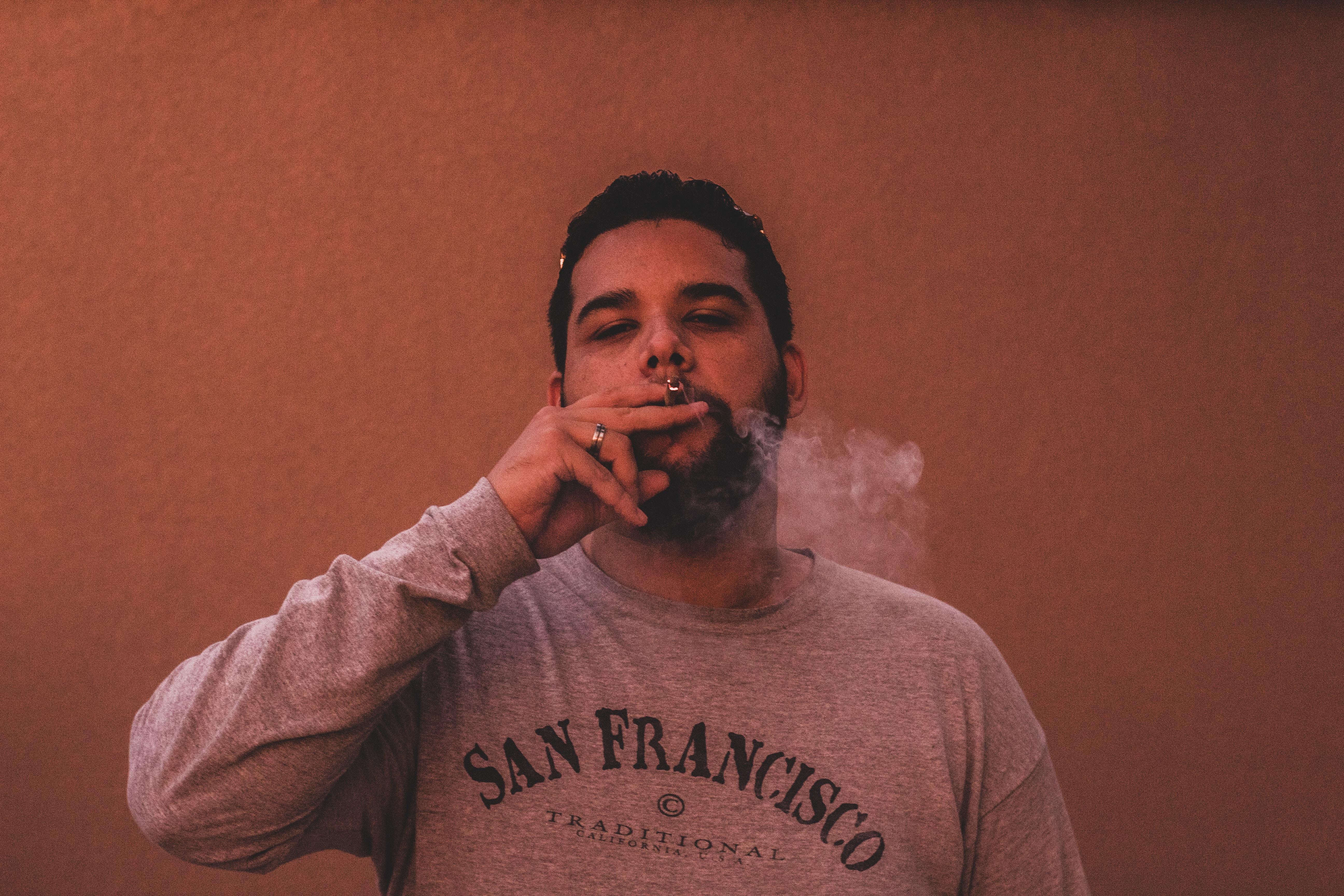 man wearing gray San Francisco long-sleeved shirt while smoking