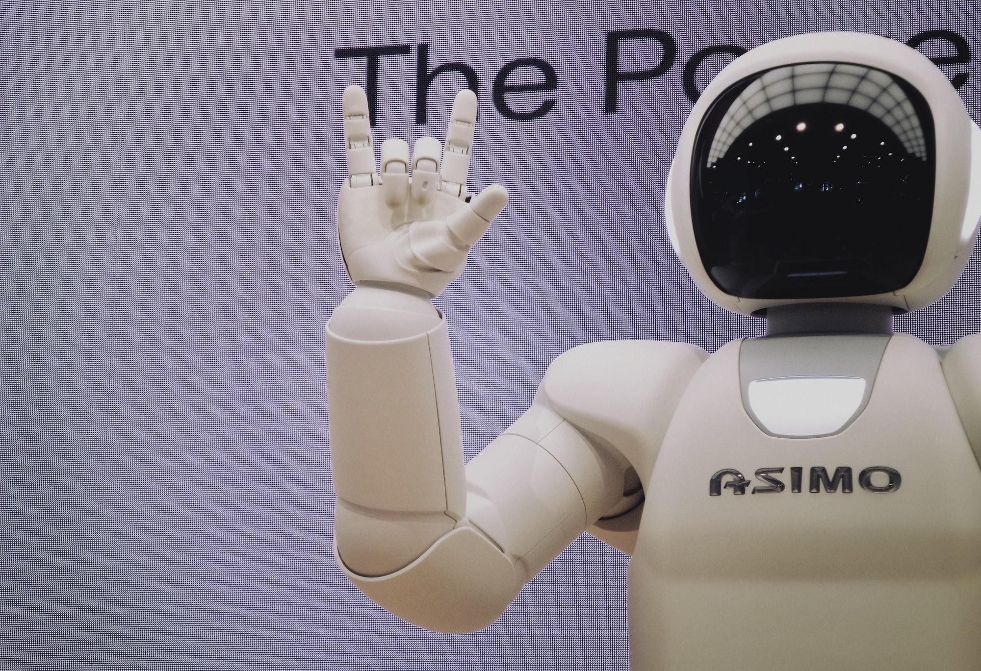 Robô humano com estética de astronauta, todo branco e capacete redondo com viseira escura, fazendo um sinal  com a mçao.