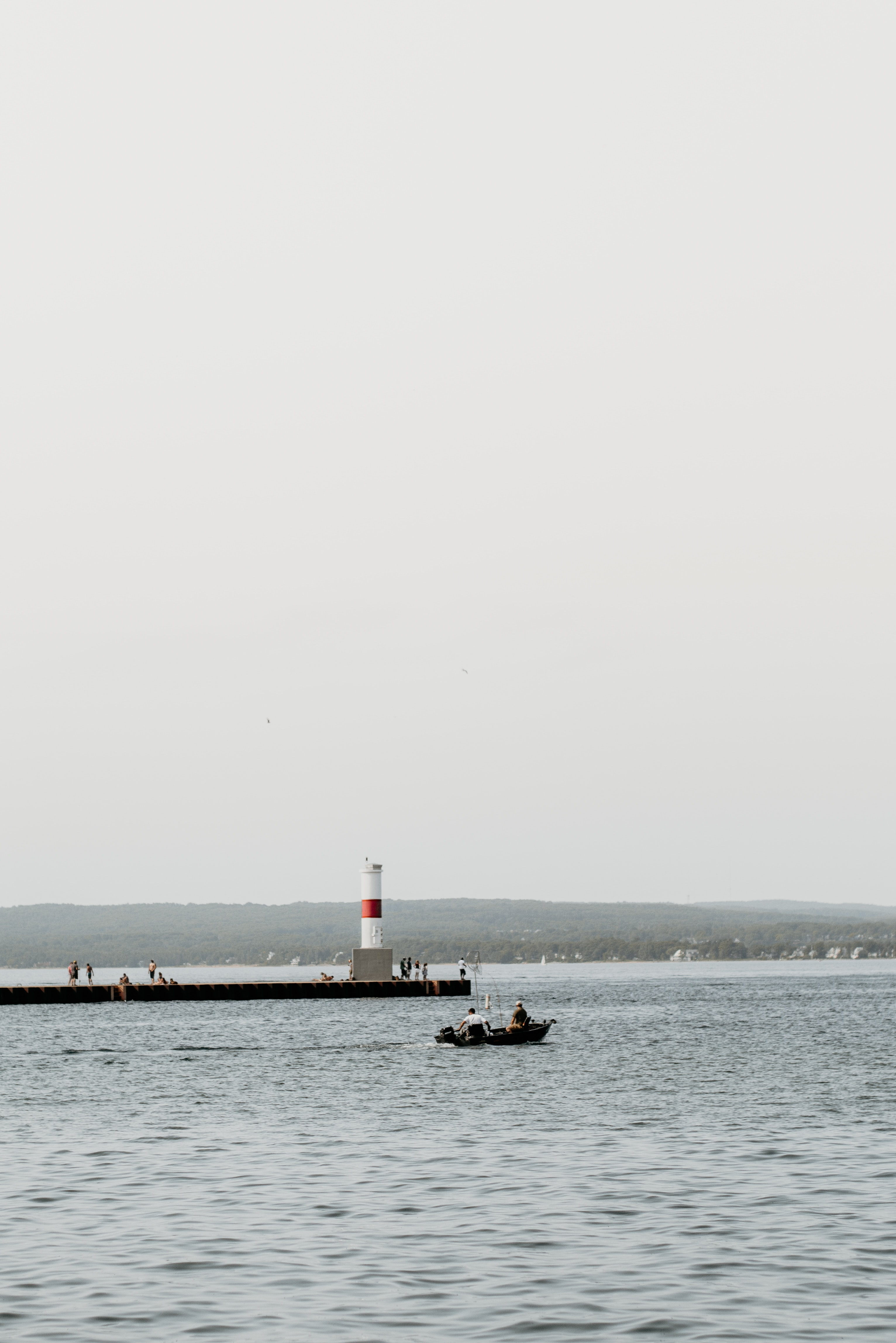 boat on body of water with lighthouse background