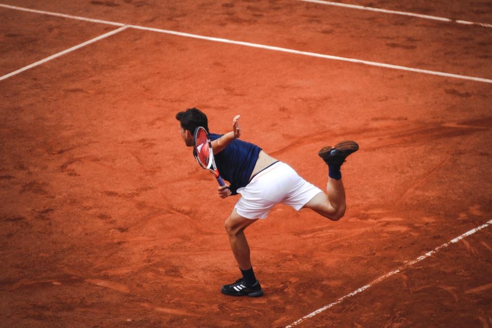 man playing tennis inside field