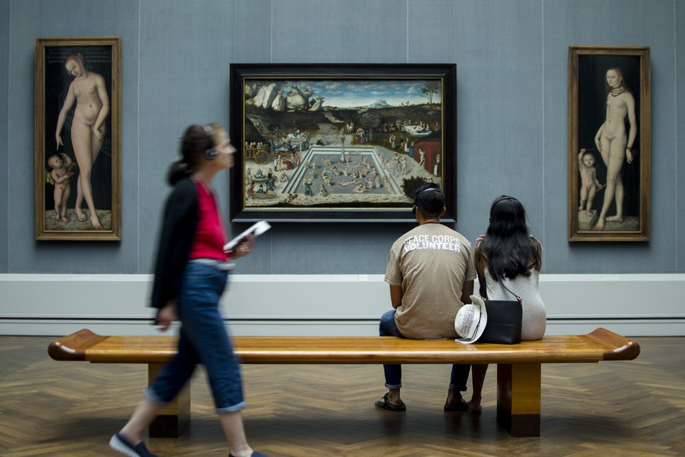 man and woman sitting on bench while looking at painting