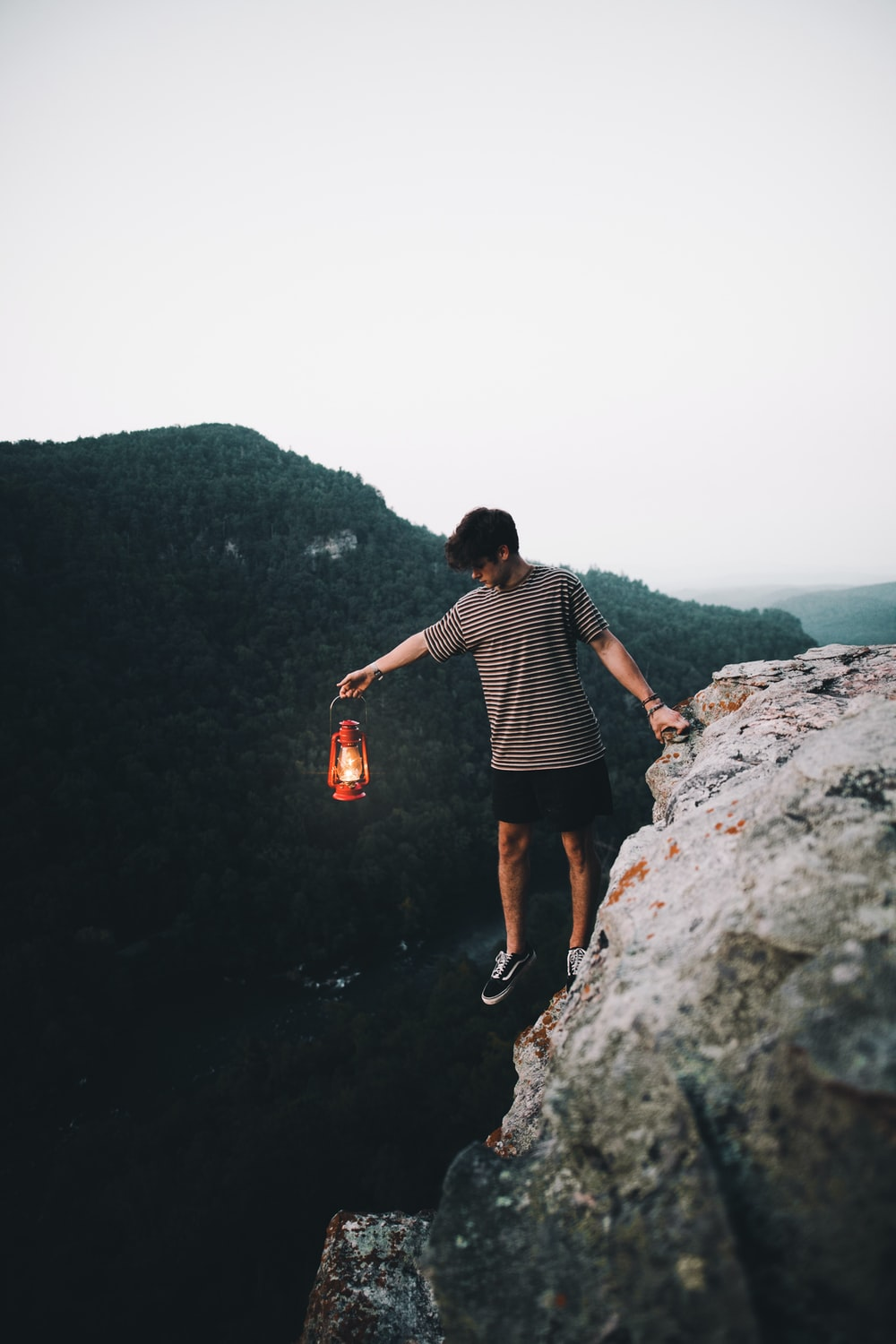 person holding lantern on cliff