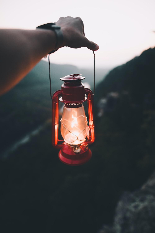 person holding red kerosene lamp