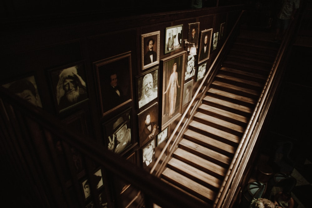 photo frames hanged on wall beside empty brown wooden stairs