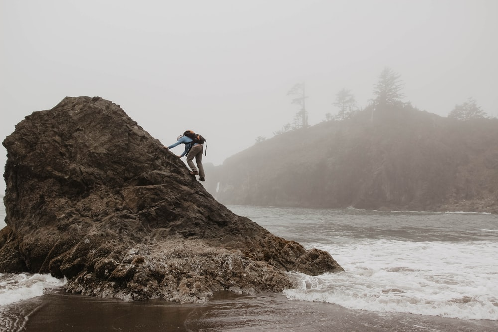 man climbing rock formation by water