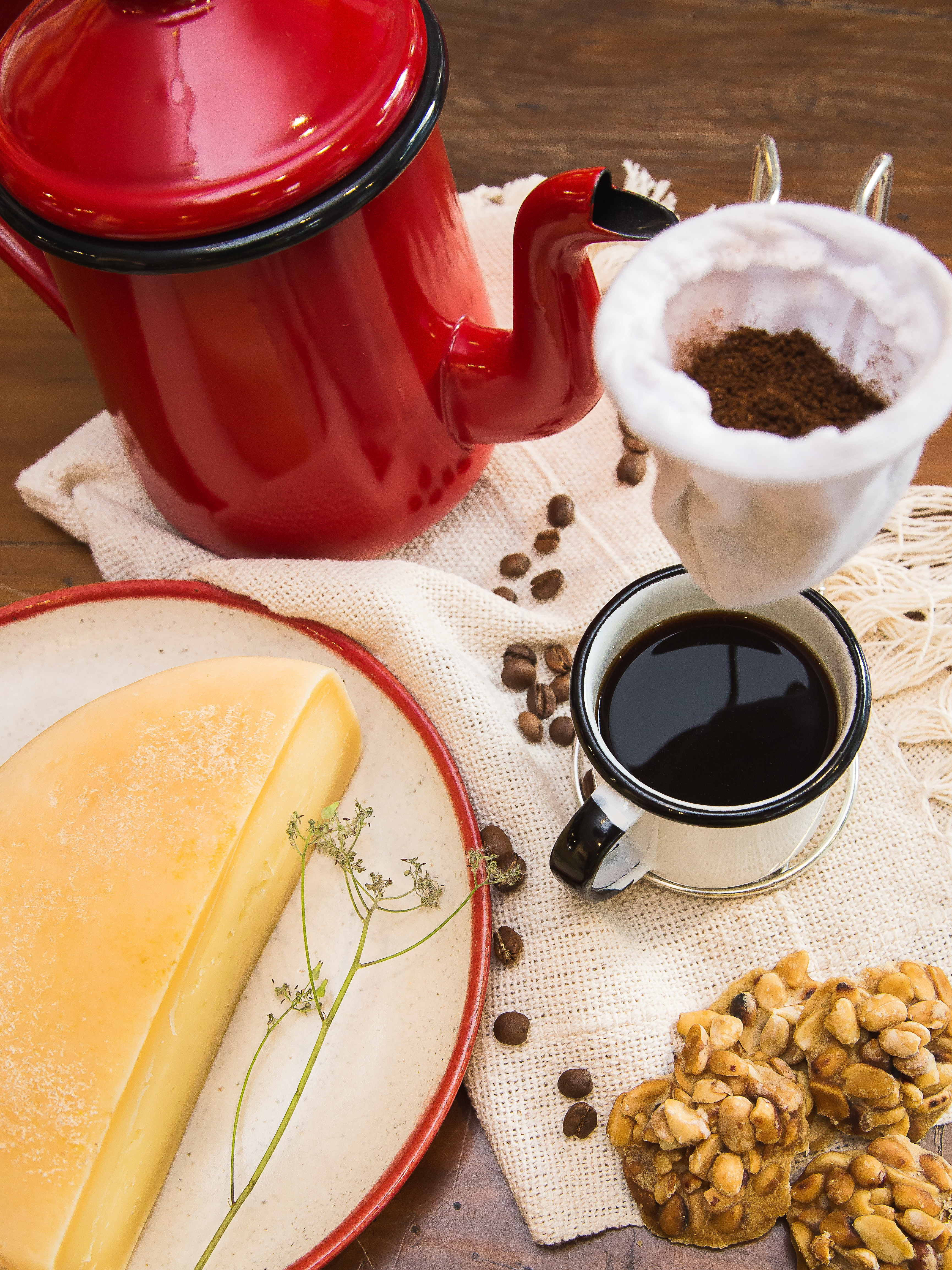 red and black kettle near mug filled with coffee and half a cheese on table