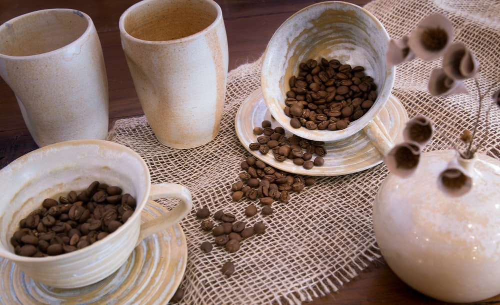 coffee beans spilled on saucer plate and table cloth near white ceramic vases
