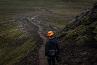 photo of man with helmet standing near mountain slope