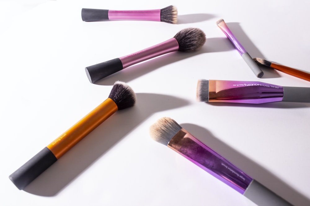 assorted-color makeup brush on white surface