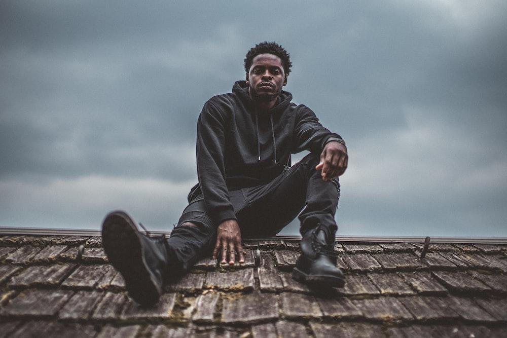 man in black pullover hoodie sitting on roof