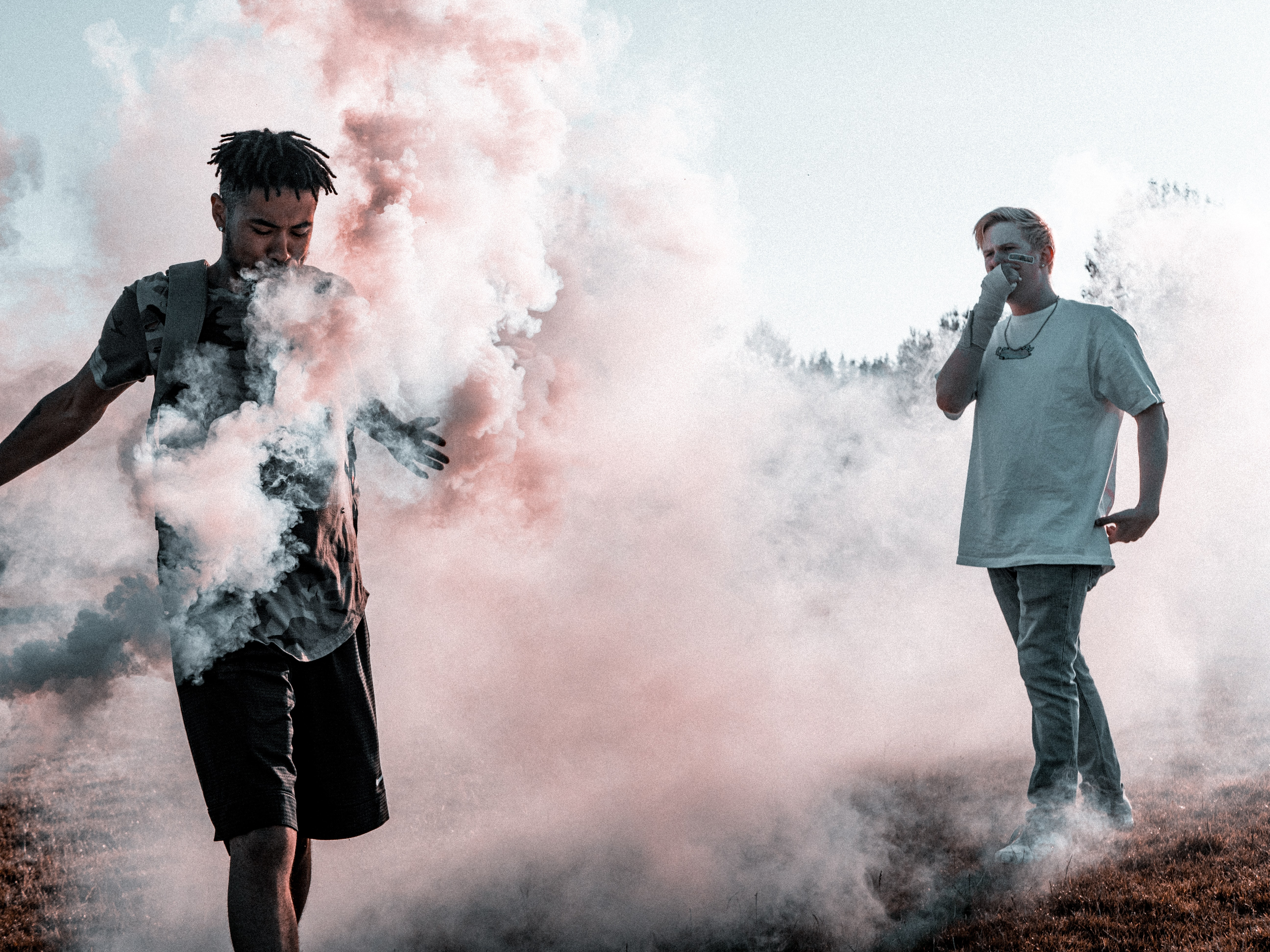 two person surrounded with smokes