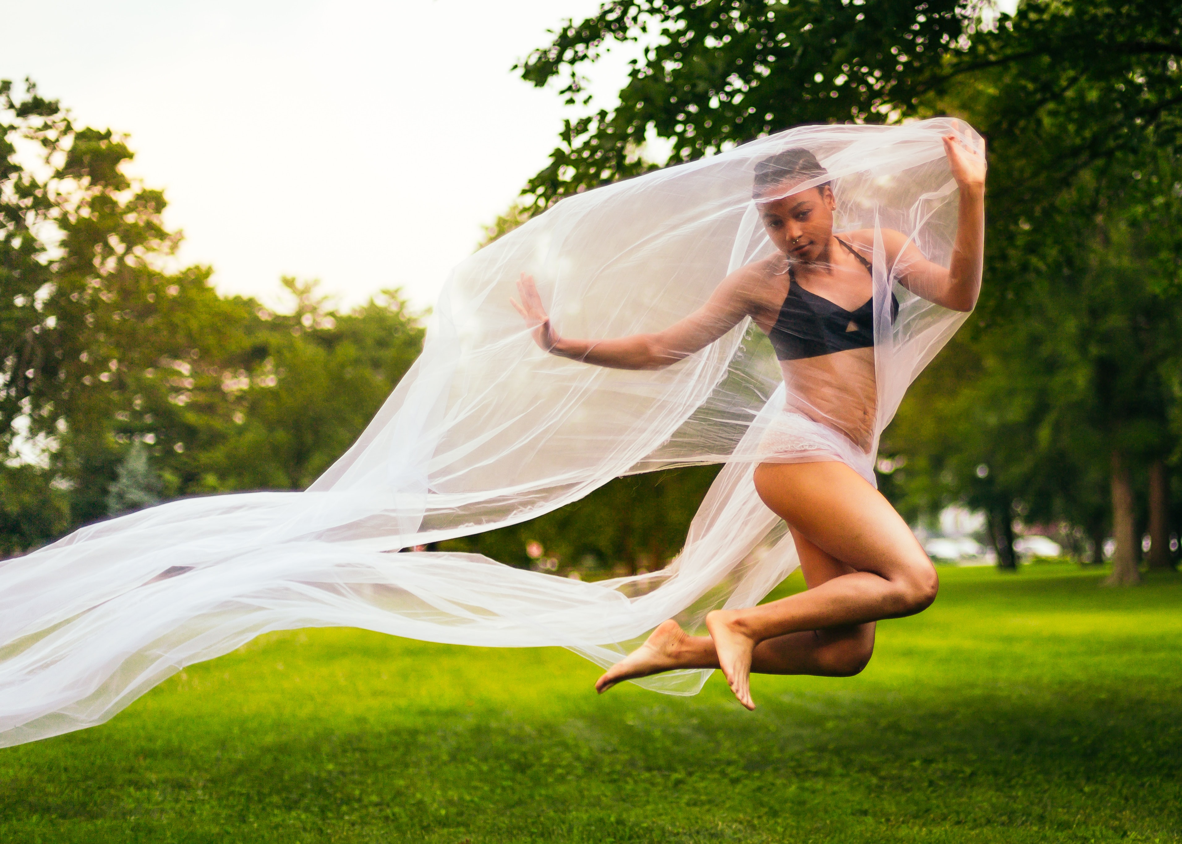 woman holding mesh cloth while jumping