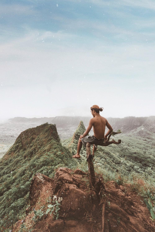 man sitting on tree branch above mountain