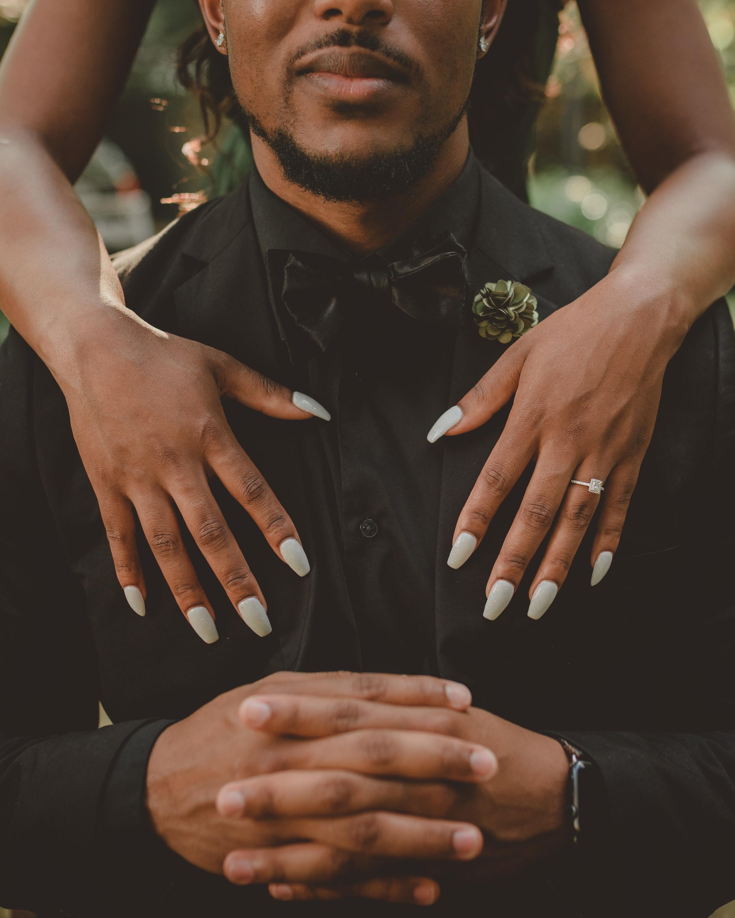 woman standing behind man in black tuxedo