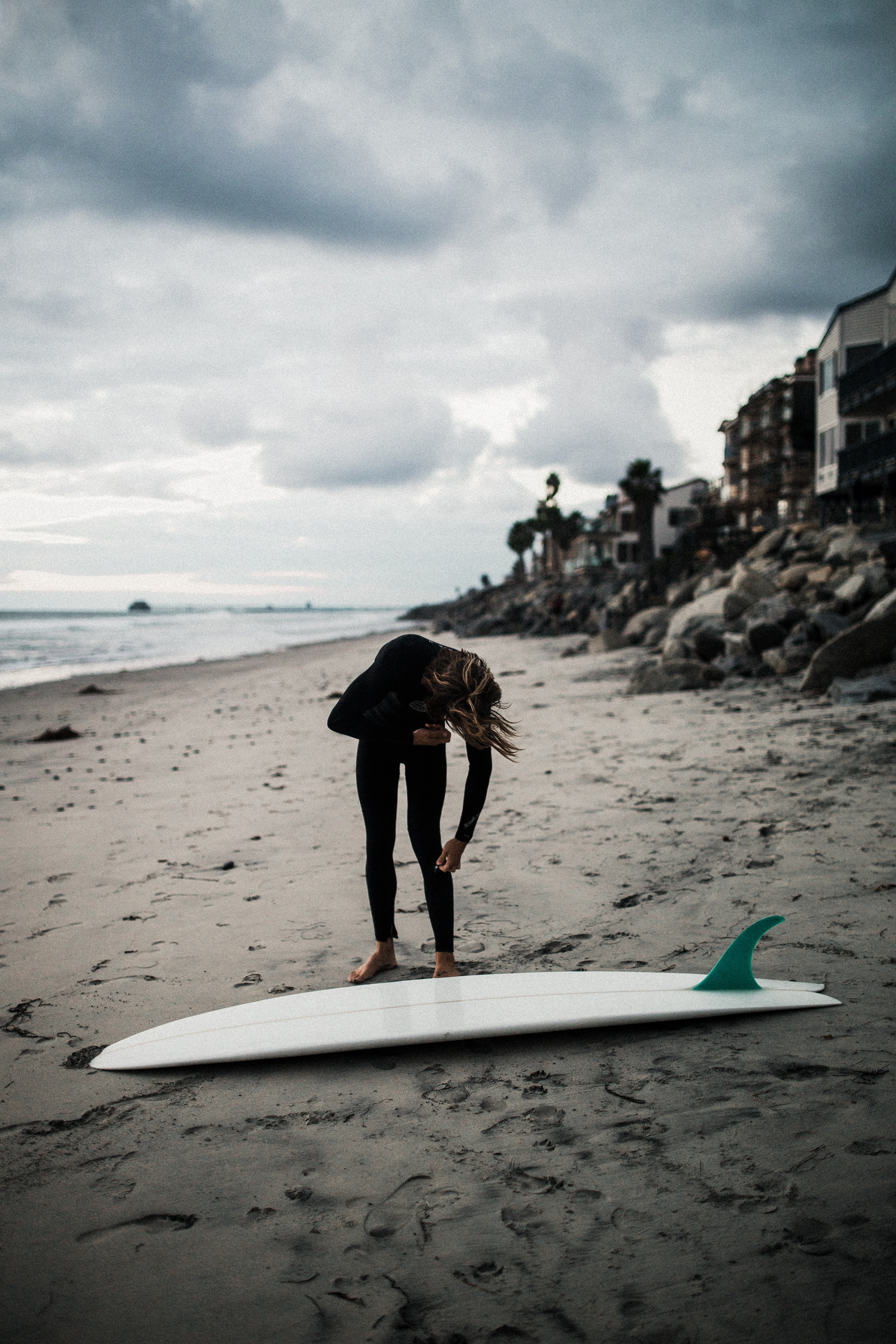 woman about to pick-up surfboard on beach