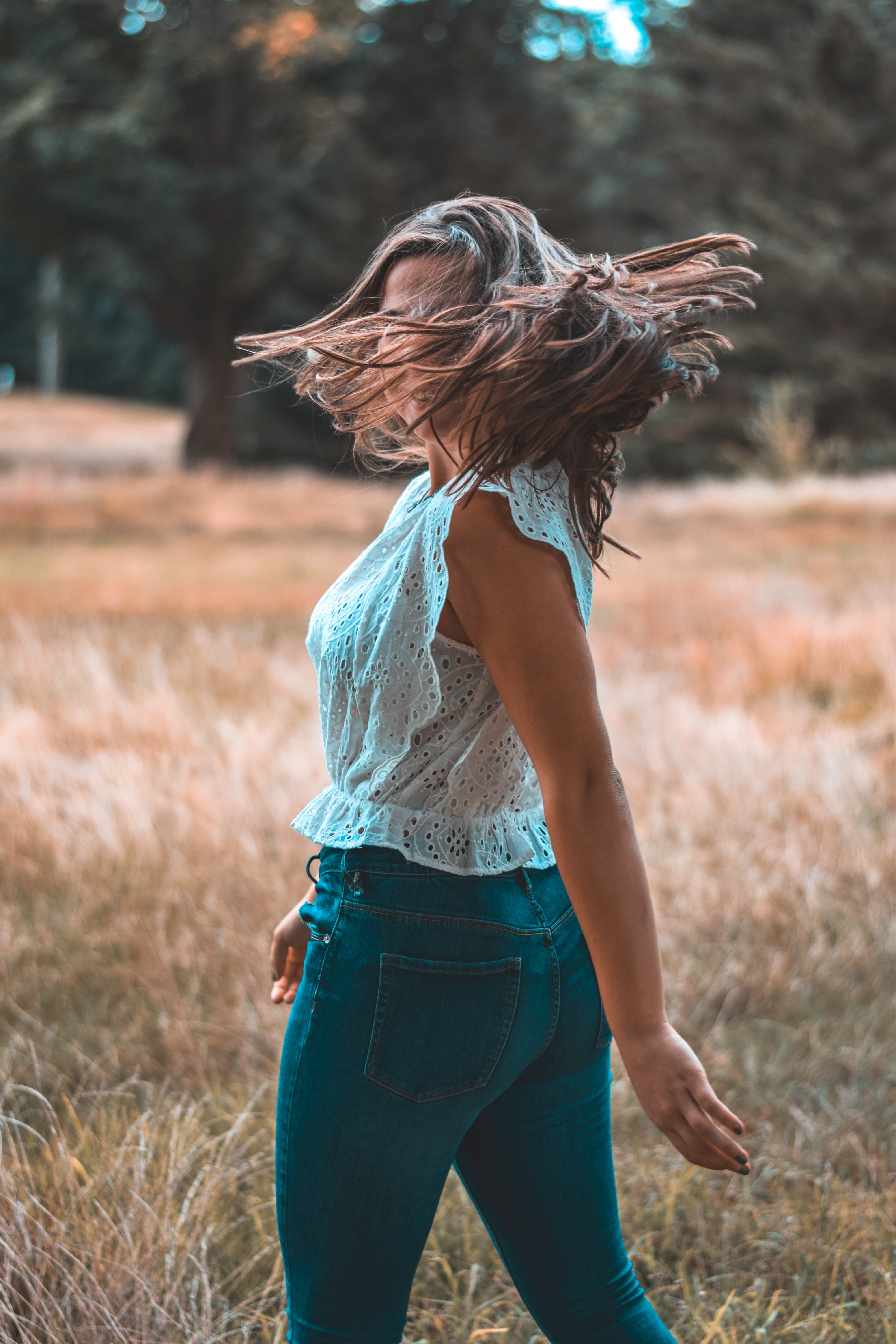 woman standing on brown grass while flipping her hair at daytime
