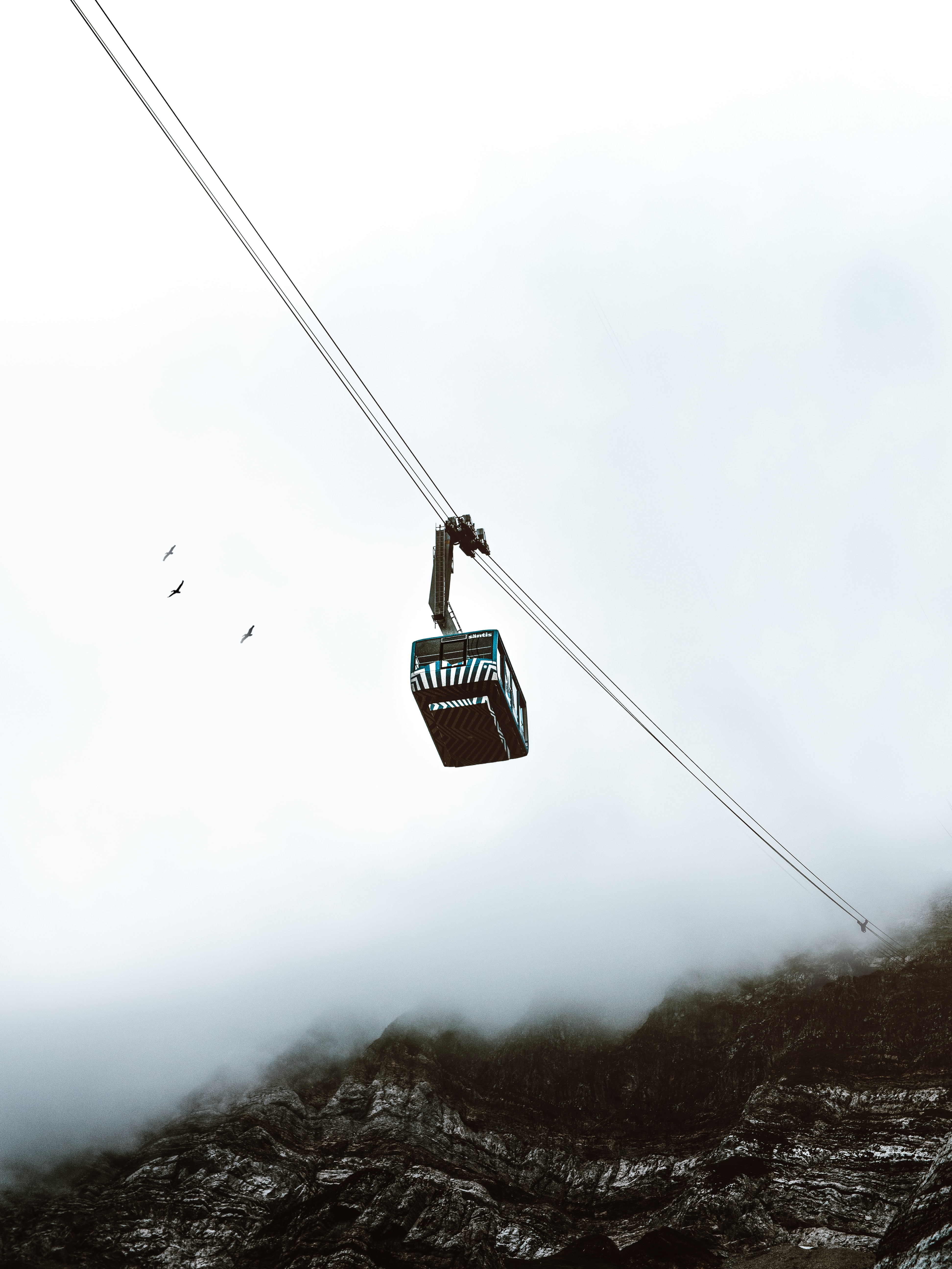worm's eye view of cable tram under gray sky
